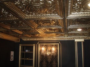Beautifuly finished basement with black walls, gold trim and ceiling tiles.